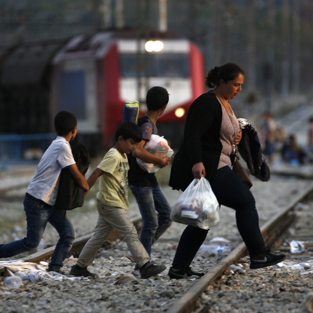 A Syrian refugee family walks across rail tracks near Greece's border with Macedonia, outside the village of Idomeni, September 7, 2015. Thousands of migrants and refugees were crowding at Greece's border with Macedonia on Monday morning, their entry slowly rationed by Macedonian police. REUTERS/Yannis Behrakis - RTX1RJAW